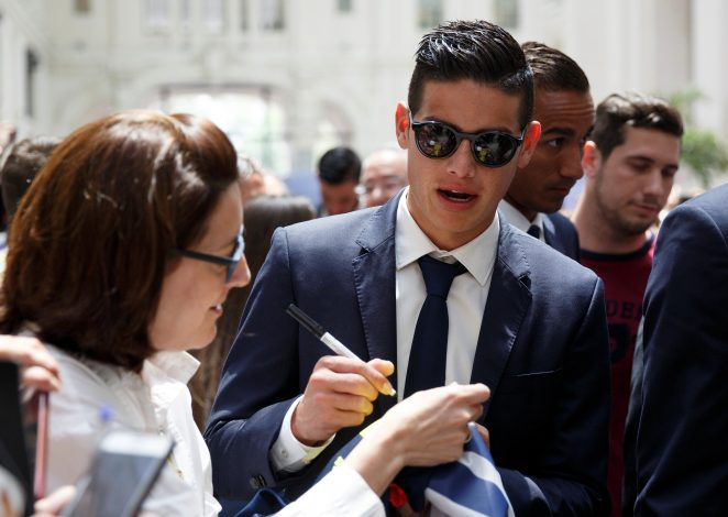 Real Madrid's James Rodriguez signs an autograph during a ceremony.