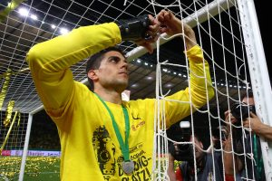 Borussia Dortmund's Marc Bartra cuts the net with a pair of scissors as he celebrates after victory.