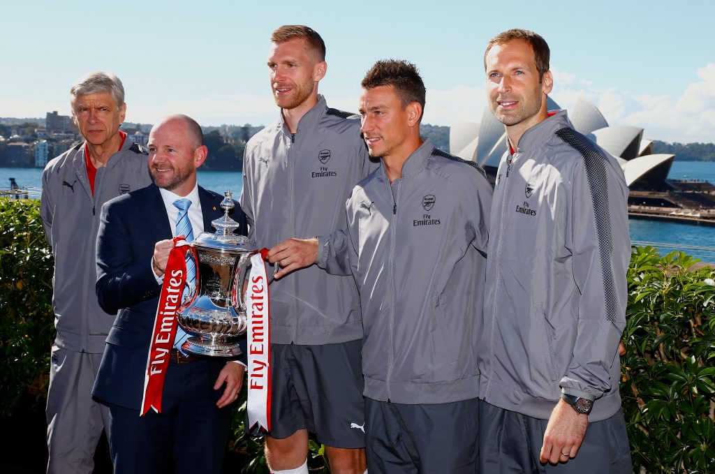 Soccer players Per Mertesacker, Laurent Koscielny and Peter Czech from English Premier League club Arsenal stand together with team manager Arsene Wenger and New South Wales Minister for Trade and Industry Niall Blair, as they pose for photographs with the FA Cup trophy in front of the Sydney Opera House in Australia, July 11, 2017.  REUTERS/David Gray - RTX3AXAS