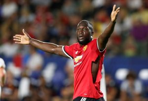 Manchester United's Romelu Lukaku gestures after his shirt is ripped.