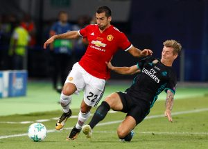 Henrikh Mkhitaryan in action with Toni Kroos.