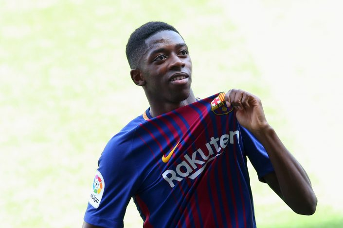 F.C. Barcelona's new signing Ousmane Dembele shows off club's seal.