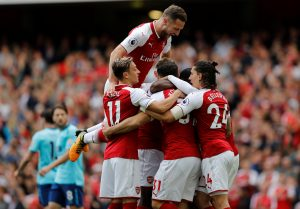 Arsenal's Danny Welbeck (hidden) celebrates scoring their first goal with team mates.