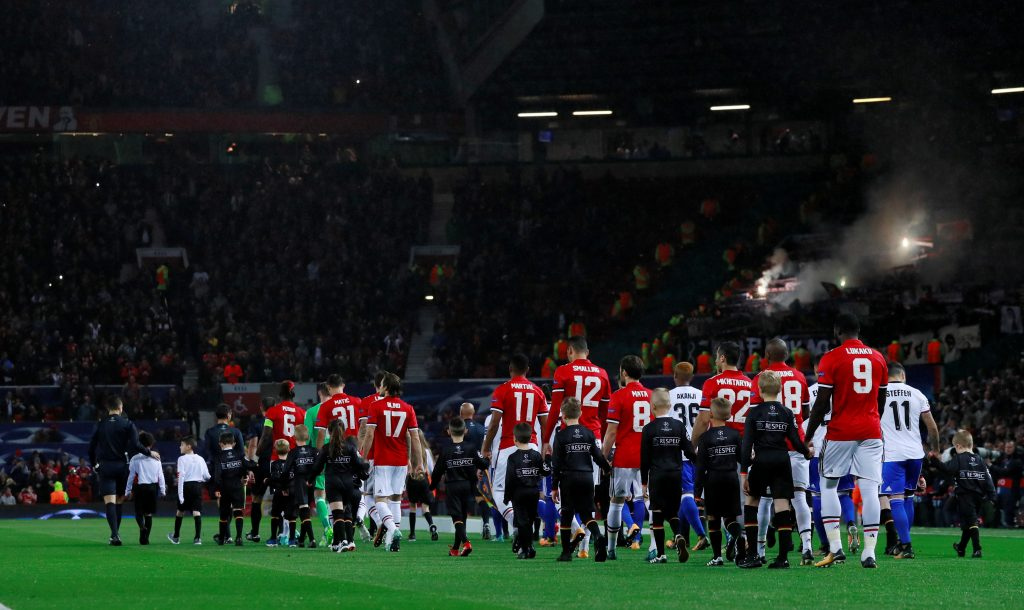 The teams walk out onto the pitch before the match.
