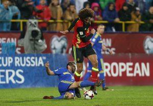 Bosnia's Senad Lulic in action with Belgium's Marouane Fellaini.