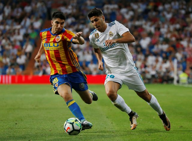 Real Madrid's Marco Asensio in action with Valencia's Carlos Soler.