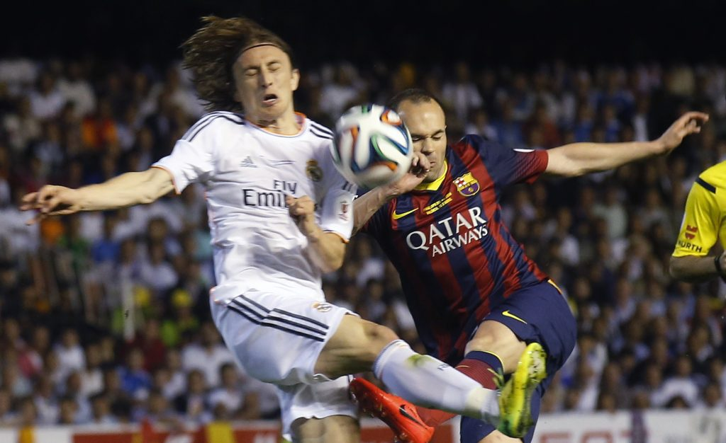 Barcelona's Andres Iniesta (R) and Real Madrid's Luka Modric challenge for the ball.
