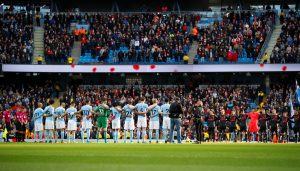 The players during a minutes silence as part of remembrance commemorations before the match.