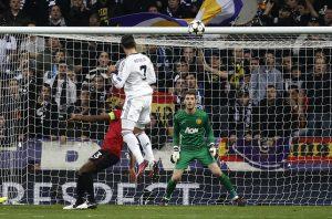 Cristiano Ronaldo scores past David De Gea (R).