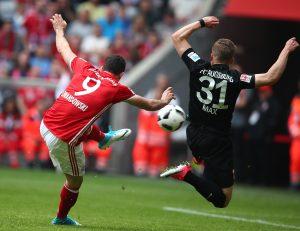 Bayern Munich's Robert Lewandowski scores a goal past Augsburg's Philipp Max.