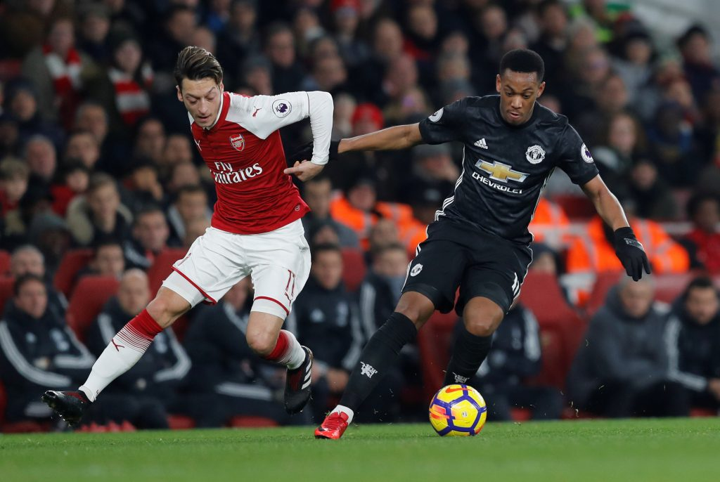 Arsenal's Mesut Ozil in action with Manchester United's Anthony Martial.