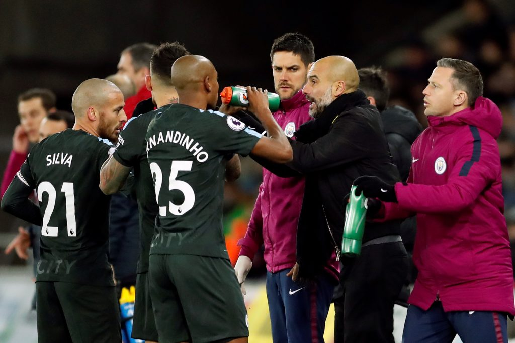 Man City manager Pep Guardiola talks to Fernandinho and David Silva during break in play.