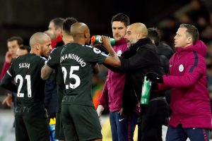 Man City manager Pep Guardiola talks to Fernandinho and David Silva during break in play.