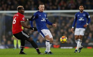 Everton's Wayne Rooney in action with Paul Pogba.