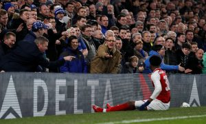 Arsenal's Ainsley Maitland-Niles as Chelsea fans gesture.