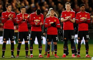 Manchester United players observe a minute's applause in memory of Jimmy Armfield before the match.