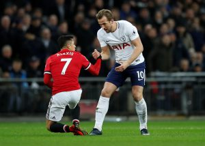 Tottenham's Harry Kane helps up Manchester United's Alexis Sanchez.