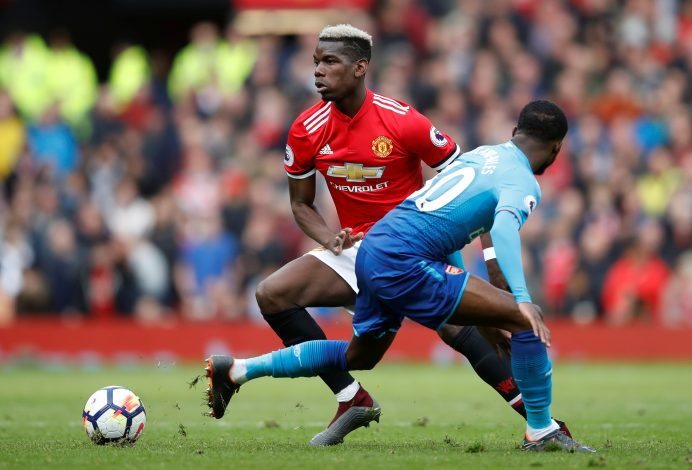 Paul Pogba in action with Arsenal's Ainsley Maitland-Niles.