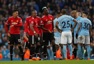 Manchester United's Paul Pogba speaks with Manchester City's Fernandinho.