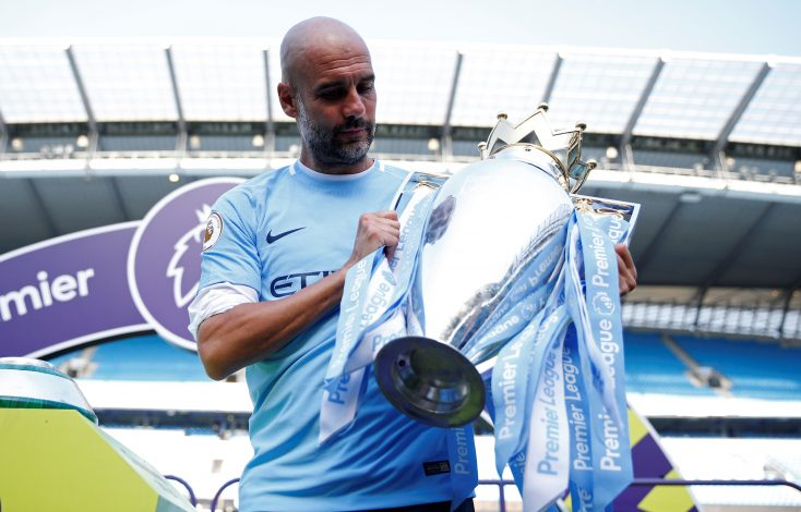 Manchester City manager Pep Guardiola celebrates with the trophy after winning the Premier League title.