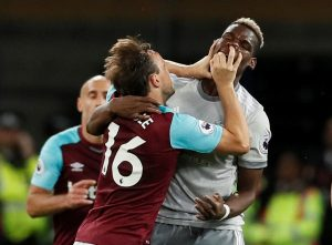 West Ham United's Mark Noble clashes with Manchester United's Paul Pogba.