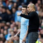 Manchester City's Phil Foden is spoken to by manager Pep Guardiola before he comes on as substitute.