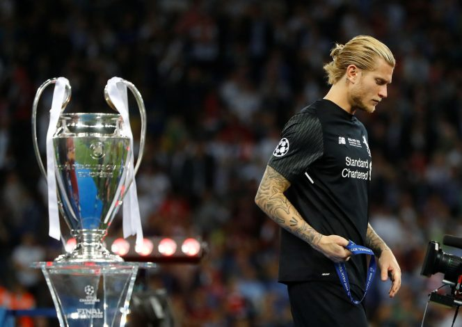 Liverpool's Loris Karius walks past the trophy with his medal after the match.