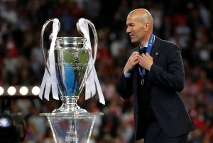 Real Madrid coach Zinedine Zidane walks past the trophy during the medal ceremony after winning the Champions League.