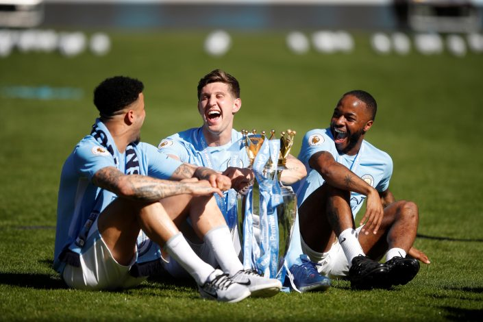 Man City's John Stones, Kyle Walker and Raheem Sterling celebrate with the trophy after winning the Premier League title.