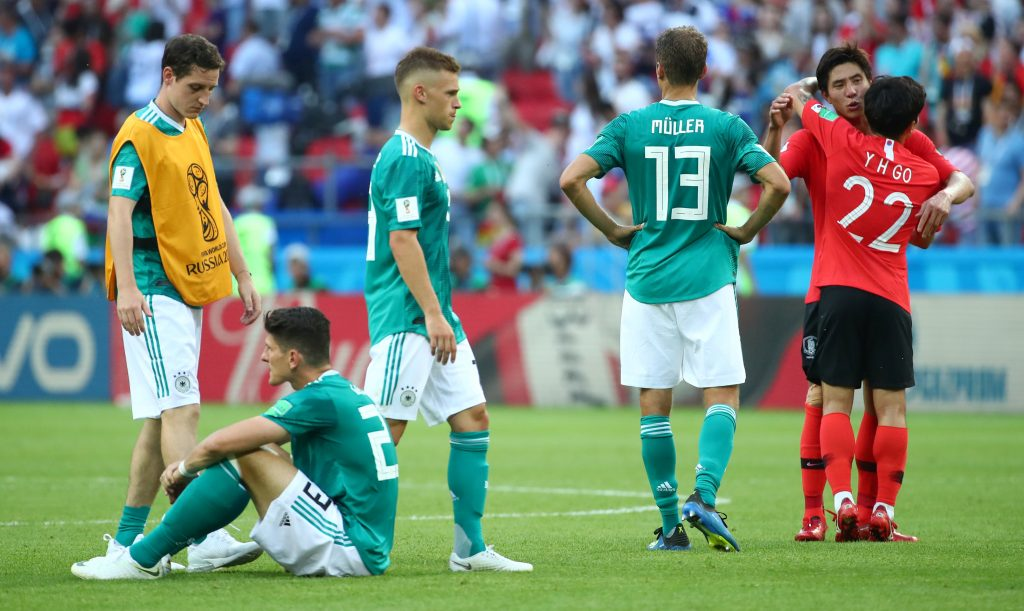Soccer Football - World Cup - Group F - South Korea vs Germany - Kazan Arena, Kazan, Russia - June 27, 2018   Germany players look dejected as South Korea players celebrate after the match    REUTERS/Michael Dalder - RC1874592B00