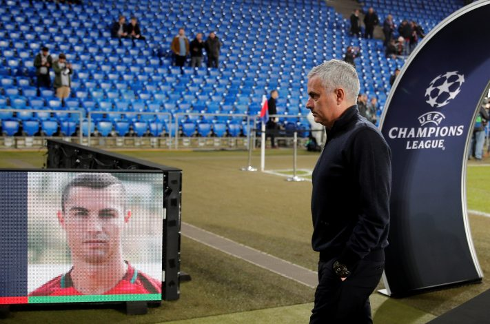 Jose Mourinho walks past a picture of Cristiano Ronaldo before the match.