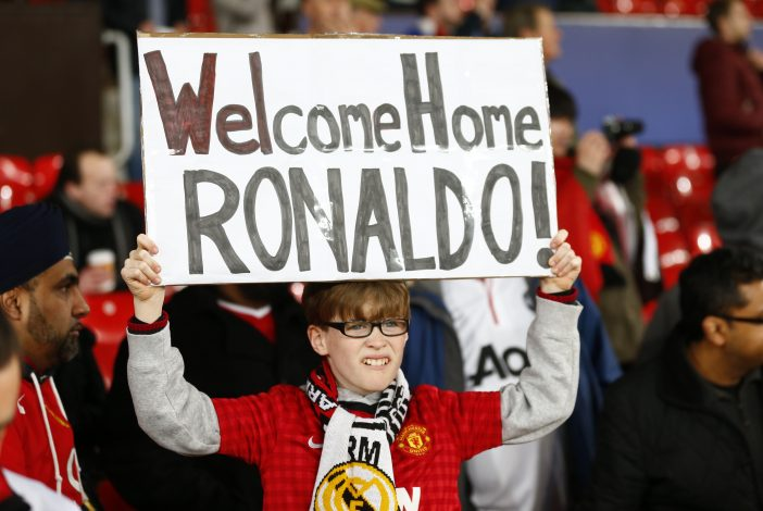 A Manchester United fan with a banner directed at Real Madrid's Cristiano Ronaldo.