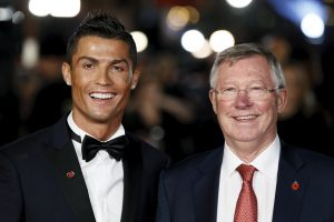 Soccer player Cristiano Ronaldo (L) and Sir Alex Ferguson pose for photographers on the red carpet.