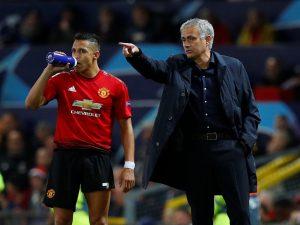 Jose Mourinho gestures while Alexis Sanchez looks on.