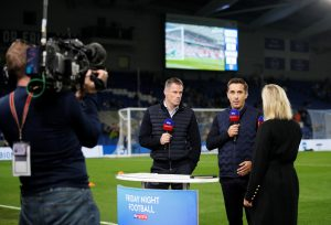 Jamie Carragher and Gary Neville performing media duties beside the pitch before the match.