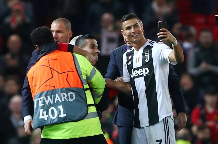 Juventus' Cristiano Ronaldo takes a selfie as stewards apprehend a pitch invader after the match.