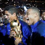 France's Kylian Mbappe and Raphael Varane celebrate with the World Cup trophy during a ceremony after the match.