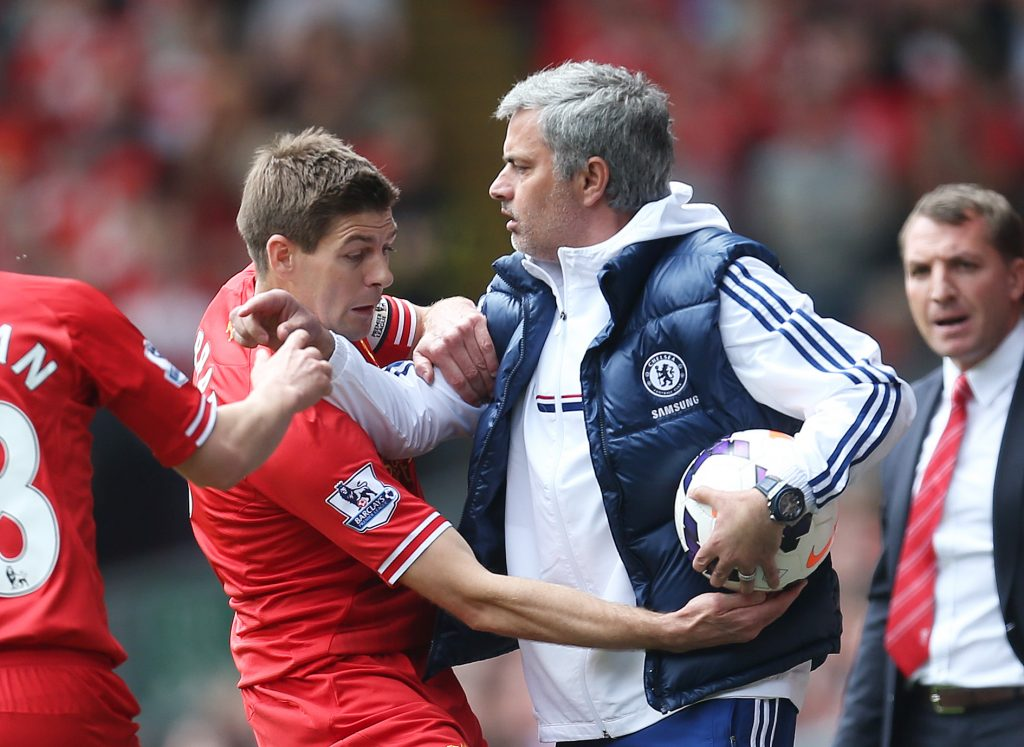 Liverpool's Steven Gerrard (L) attempts to get the ball off Chelsea manager Jose Mourinho.