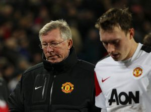 Manchester United's manager Sir Alex Ferguson (L) and Phil Jones dejected at half time.
