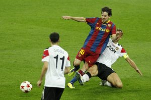 Barcelona's Lionel Messi (C) in action with Manchester United's Nemanja Vidic (R).