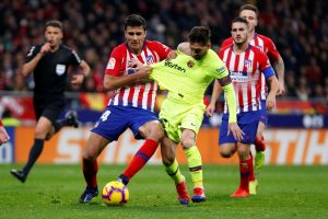 Atletico Madrid's Rodri in action with Barcelona's Lionel Messi.