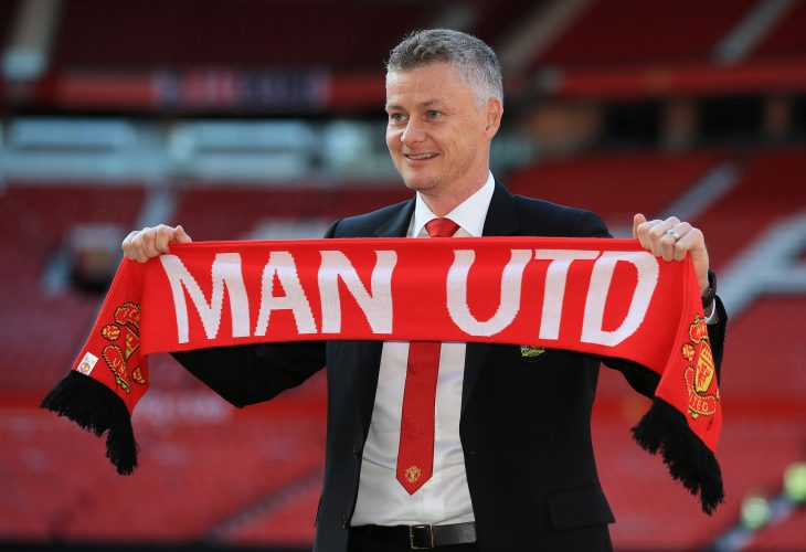 Manchester United manager Ole Gunnar Solskjaer poses with a scarf on the pitch.