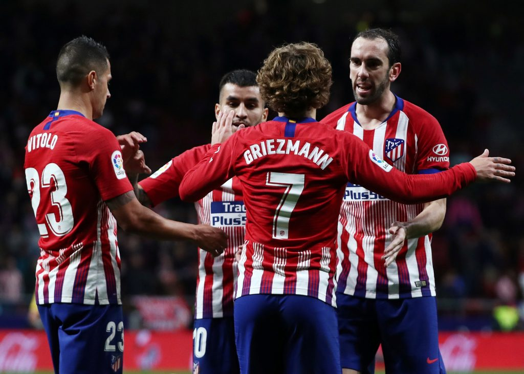 Atletico Madrid's Antoine Griezmann celebrates scoring their second goal with Diego Godin and team mates.