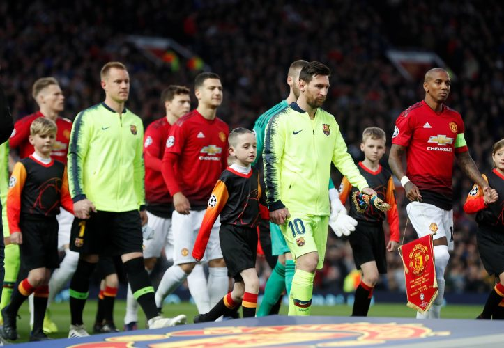 Barcelona's Lionel Messi and Manchester United's Ashley Young walk on to the pitch.