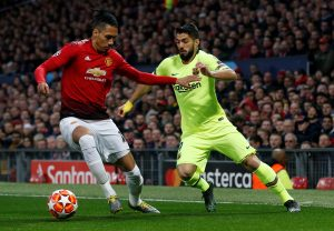 Barcelona's Luis Suarez in action with Manchester United's Chris Smalling.