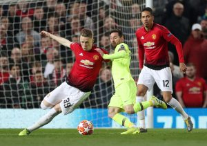 Manchester United's Scott McTominay and Chris Smalling in action with Barcelona's Lionel Messi.