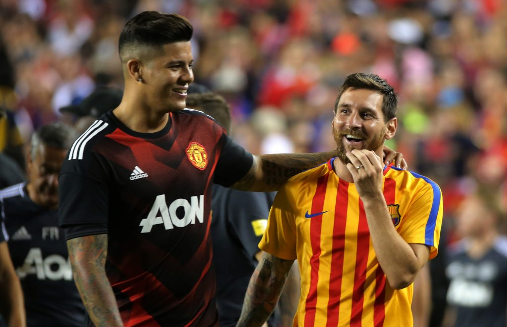 Manchester United's Marcos Rojo and Barcelona's Lionel Messi after the game.