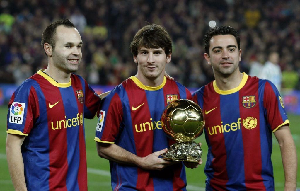Barcelona's Lionel Messi poses with his Ballon d'Or trophy next to his teammates Andres Iniesta (L) and Xavi Hernandez.