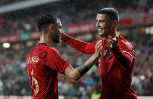 Portugal's Bruno Fernandes celebrates with Cristiano Ronaldo after scoring their second goal.