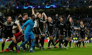 Ajax players celebrate in front of their fans at the end of the match.